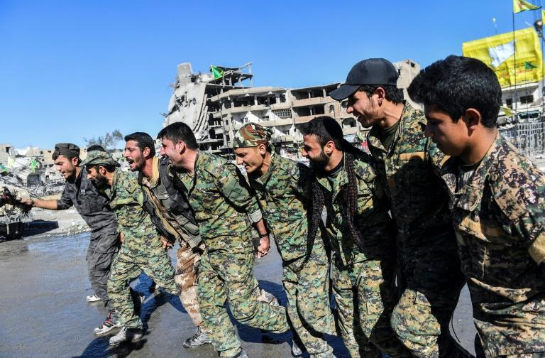 Members of the Syrian Democratic Forces (SDF) celebrate on the iconic Al-Naim square in Raqa on October 18, 2017, after retaking the city from Islamic State group