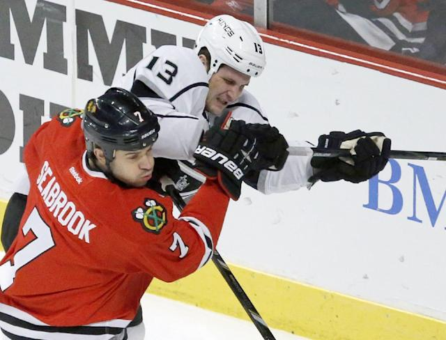 Chicago Blackhawks defenseman Brent Seabrook (7) and Los Angeles Kings left wing Kyle Clifford battle for a loose puck during the first period of an NHL hockey game Monday, Dec. 30, 2013, in Chicago. (AP Photo/Charles Rex Arbogast)