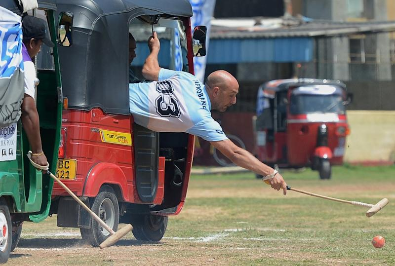 Players take part in a tuk-tuk (three-wheeler) polo match in Galle on February 21, 2016 (AFP Photo/Lakruwan Wanniarachchi)