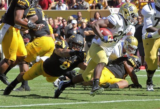 UCLA running back Johnathan Franklin (23) scores a touchdown as Arizona State linebacker Brandon Magee (8) reaches for him during the first half of an NCAA college football game, Saturday, Oct. 27, 2012, in Tempe, Ariz. (AP Photo/Matt York)