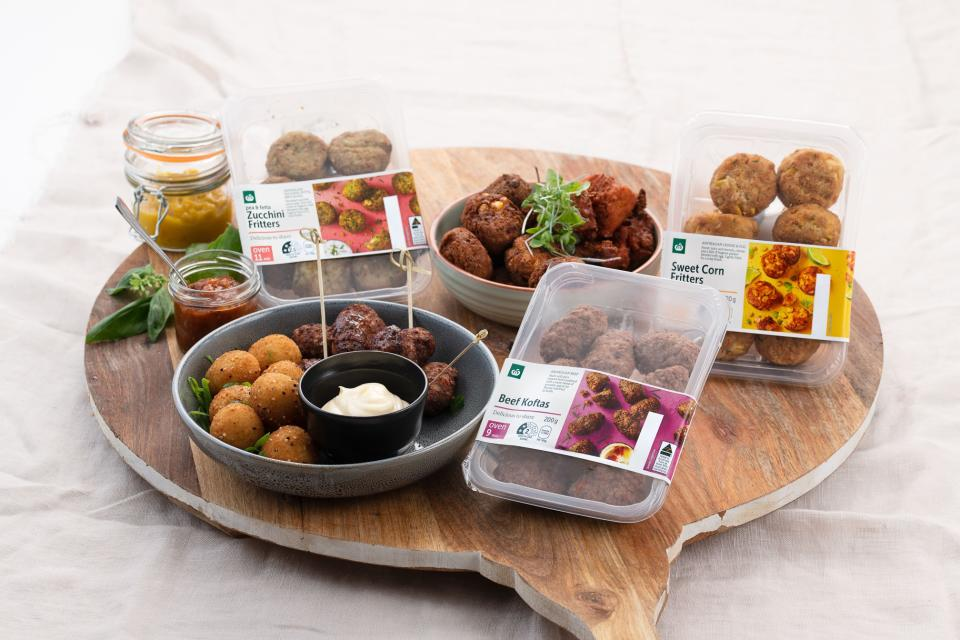 Woolworths beef koftas, sweet corn fritters and zucchini fritters are seen on a wooden platter.