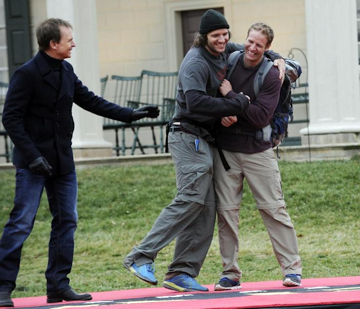 """In this publicity image released by CBS, host Phil Keoghan, left, greets brothers Bates, center, and Anthony at the finish line at the historic home of President George Washington in Mount Vernon, Va., on the 22nd season finale of """"The Amazing Race."""" The program was nominated for an Emmy Award for outstanding reality-competition program, Thursday July 18, 2013. The Academy of Television Arts & Sciences' Emmy ceremony will be hosted by Neil Patrick Harris. It will air Sept. 22 on CBS. (AP Photo/CBS, Heather Wines)"""