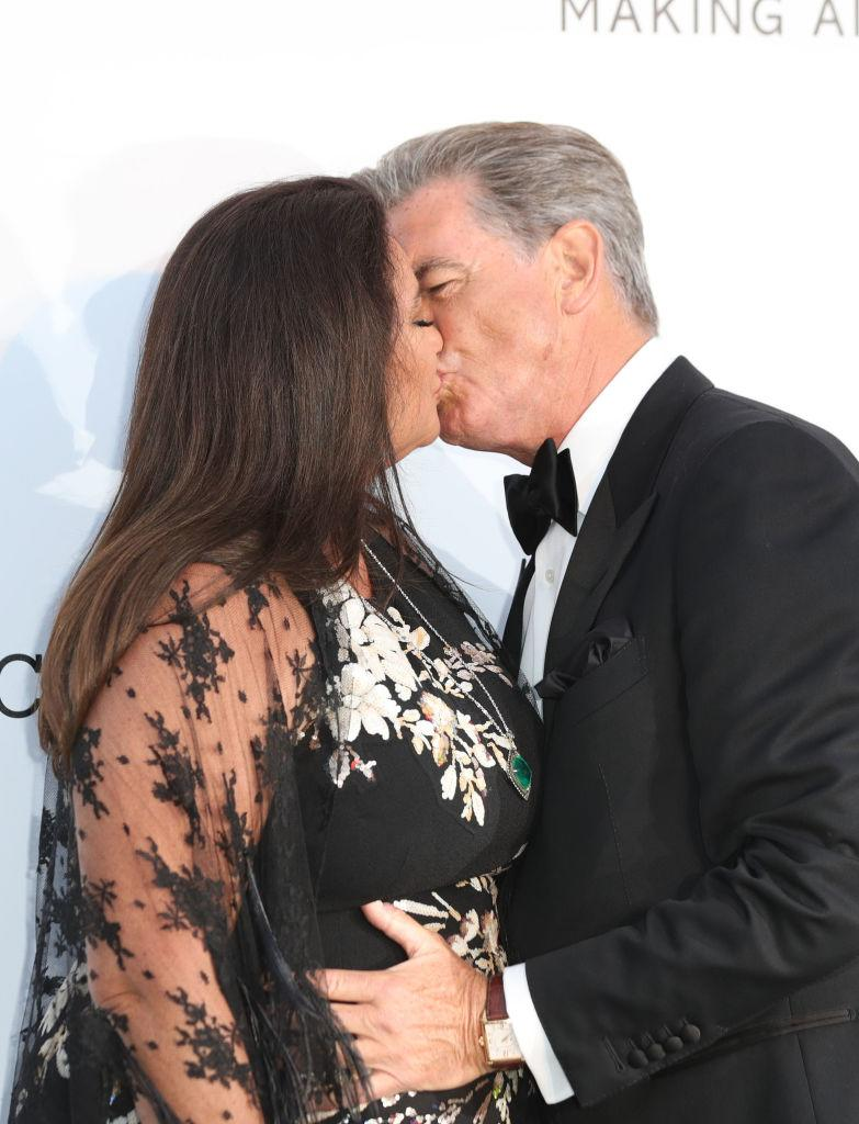 Pierce Brosnan and his wife share a tender kiss, pictured in May 2018 in Cannes. (Getty Images)