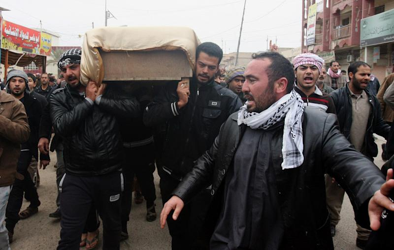Mourners carry the coffin of a man killed when clashes erupted between al-Qaida gunmen and Iraqi army soldiers on Friday, his family said, during his funeral in Fallujah, 40 miles (65 kilometers) west of Baghdad, Iraq, Saturday, Jan. 4, 2014. Provincial spokesman Dhari al-Rishawi said Iraqi security forces and allied tribesmen are pressing their campaign to rout al-Qaida from Fallujah and Ramadi, two main cities in the western Anbar province. (AP Photo)