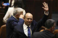 Israel's new prime minister Naftali Bennett raises his hand during a Knesset session in Jerusalem Sunday, June 13, 2021. Israel's parliament has voted in favor of a new coalition government, formally ending Prime Minister Benjamin Netanyahu's historic 12-year rule. Naftali Bennett, a former ally of Netanyahu became the new prime minister (AP Photo/Ariel Schalit)