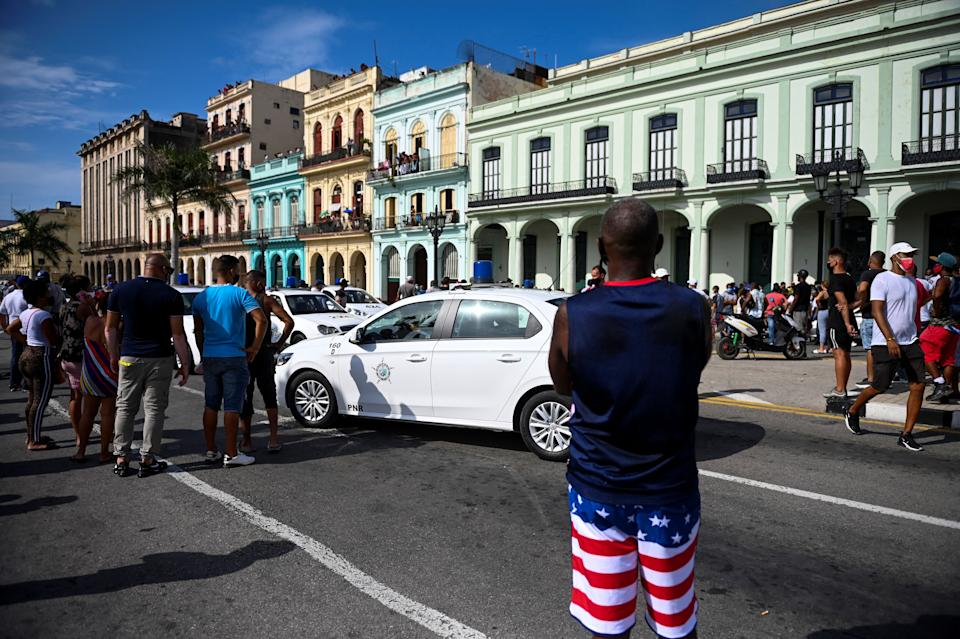 Cubans march in front of Havana's Capitol during a demonstration against the government of Cuban President Miguel Diaz-Canel in Havana, on July 11, 2021. - Thousands of Cubans took part in rare protests Sunday against the communist government, marching through a town chanting