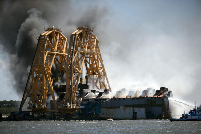 Firefighters hose down a fire in the remains of the overturned cargo ship Golden Ray, Friday, May 14, 2021, Brunswick, Ga. The Golden Ray had roughly 4,200 vehicles in its cargo decks when it capsized off St. Simons Island on Sept. 8, 2019. Coast Guard Petty Officer 2nd Class Michael Himes says there have been no injuries and all demolition crew members were safely evacuated. (AP Photo/Stephen B. Morton)
