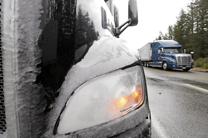 A truck remains partially covered with ice and parked after being forced to turn around on Snoqualmie Pass when Interstate 90 closed earlier Wednesday, Jan. 18, 2017, in North Bend, Wash. An ice storm shut down parts of major highways and interstates Wednesday in Oregon and Washington state and paralyzed the hardest hit towns along the Columbia River Gorge with up to 2 inches of ice coating the ground in some places. In Washington state, I-90, the main highway connecting western and eastern Washington, was to remain closed over Snoqualmie Pass because of hazardous winter conditions. (AP Photo/Elaine Thompson)