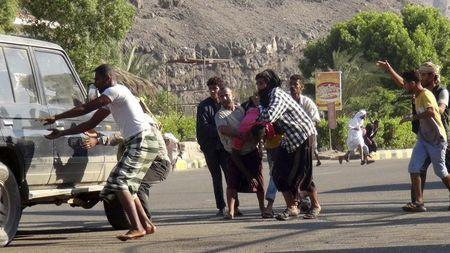 People carry a man injured during a gunfire at an army base in Yemen's southern port city of Aden March 25, 2015. REUTERS/Anees Mansour