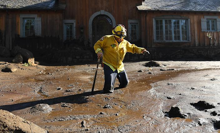 <p>Cal Firefighter Alex Jimenez walks out after finding a body under the mud at a house along Glen Oaks Drive in Montecito after a major storm hit the burn area Wednesday on Jan.10, 2018 in Montecito, California. (Photo: Wally Skalij/Los Angeles Times via Getty Images) </p>