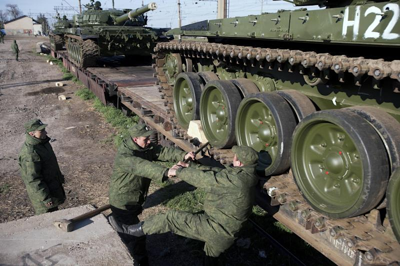 Russian solders prepare to move a Russian tank T-72B at the Ostryakovo railway station not far from Simferopol, Crimea, Monday, March 31, 2014. Russian tanks T-72B will be stationed on former Ukrainian military bases. (AP Photo/Pavel Golovkin)