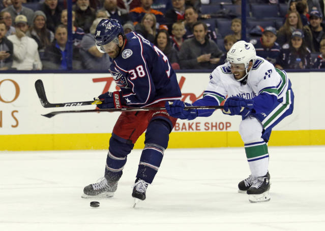 Columbus Blue Jackets forward Boone Jenner, left, chases the puck against Vancouver Canucks forward Josh Leivo during the second period of an NHL hockey game in Columbus, Ohio, Tuesday, Dec. 11, 2018. (AP Photo/Paul Vernon)