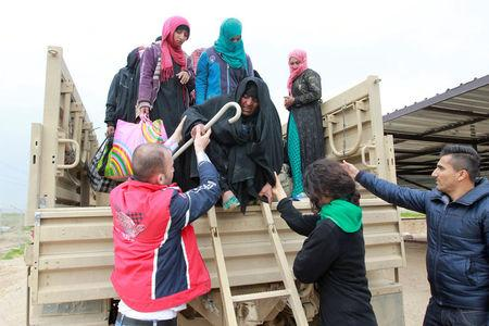Displaced Iraqi people who fled Islamic State militants arrive in Kirkuk to be transported to camps for displaced people