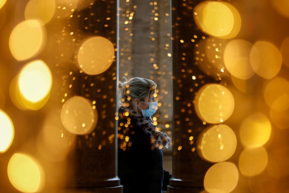 A woman wearing a protective mask is seen through a glass at a shopping centre on the day Italian Health Minister Roberto Speranza lays out in parliament the government's plan for mass coronavirus disease (COVID-19) vaccinations and restrictions over the Christmas period, in Rome, Italy December 2, 2020. REUTERS/Yara Nardi     TPX IMAGES OF THE DAY