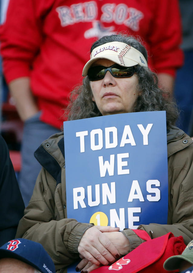 A Boston Red Sox fan holds a sign supporting the Boston Marathon runners before a baseball game between the Red Sox and Baltimore Orioles at Fenway Park in Boston Monday, April 21, 2014. (AP Photo/Winslow Townson)