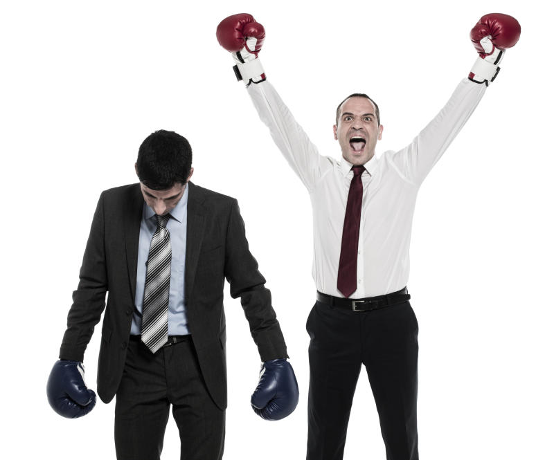 Two men in business attire are wearing boxing gloves. One man hangs his head in defeat, while the other raises his arms in victory.