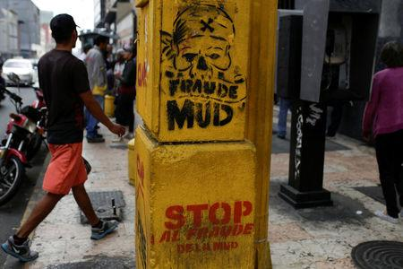 """People walk past a graffitti that reads """"Stop the fraud of the MUD"""" in Caracas"""
