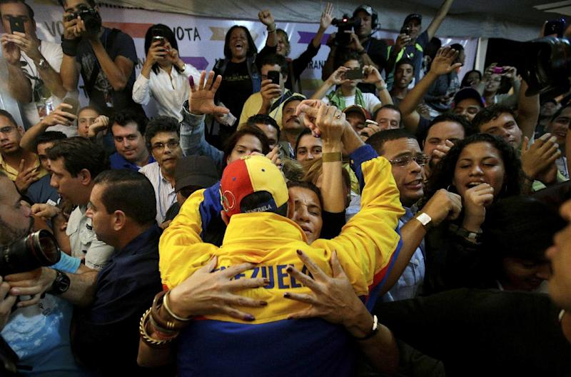 Miranda State's Gov. Henrique Capriles, center, is congratulated by his his supporters after being re-elected during an election in Caracas, Venezuela, Sunday, Dec. 16, 2012. Capriles lost to Chavez in October's presidential vote, but his re-election Sunday will allow him to cement his position as Venezuela's dominant opposition leader. (AP Photo/Fernando Llano)