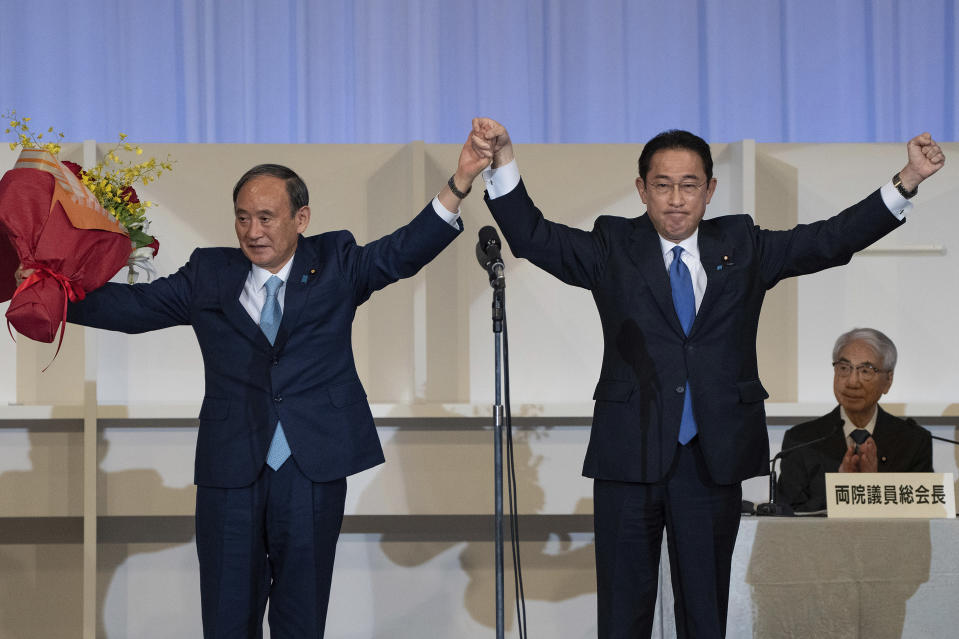 Japanese former Foreign Minister Fumio Kishida, right, celebrates with outgoing Prime Minister Yoshihide Suga after being announced the winner of the Liberal Democrat Party leadership election in Tokyo Wednesday, Sept. 29, 2021. Kishida won the governing party leadership election on Wednesday and is set to become the next prime minister, facing the imminent task of addressing a pandemic-hit economy and ensuring a strong alliance with Washington to counter growing regional security risks. (Carl Court/Pool Photo via AP)