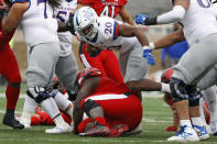 Kansas' Daniel Hishaw Jr. (20) breaks the tackle by Texas Tech's Tre'Jon Lewis (77) during the first half of an NCAA college football game Saturday, Dec. 5, 2020, in Lubbock, Texas. (AP Photo/Brad Tollefson)