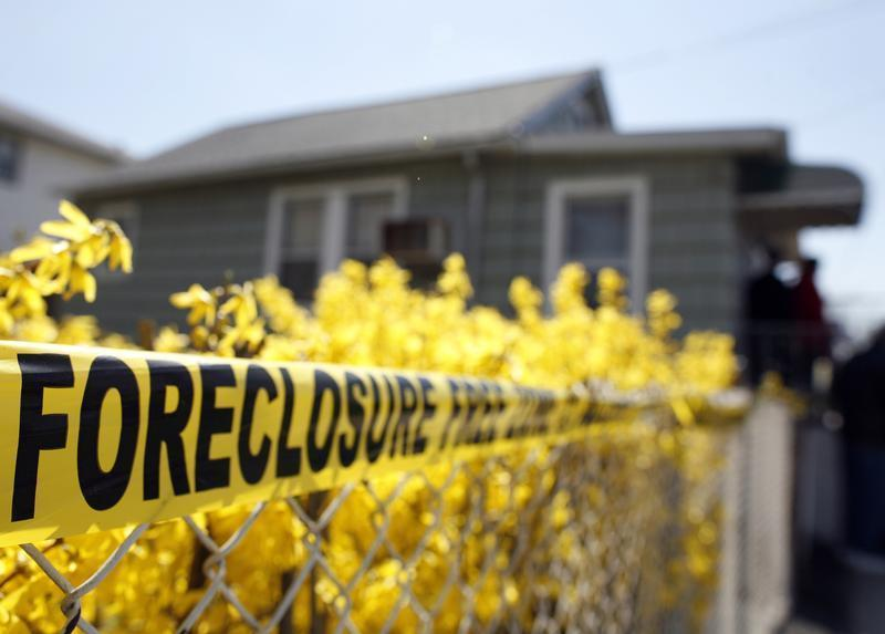 Police tape marked as a Foreclosure Free Zone is seen outside the foreclosed home of Marie Elie in Elmont