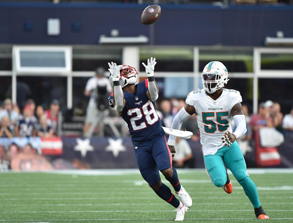Sep 12, 2021; Foxborough, Massachusetts, USA;  New England  Patriots running back James White catches the ball in front of Miami Dolphins outside linebacker Jerome Baker during the second half at Gillette Stadium in Foxboro on Sunday, Sept. 12, 2021.