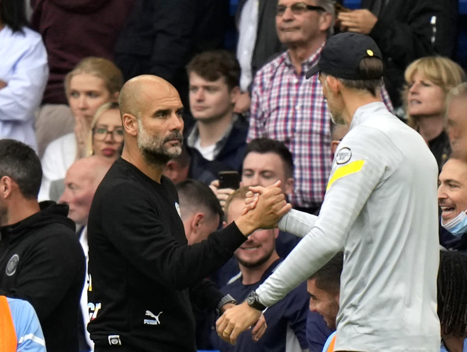 Chelsea's head coach Thomas Tuchel, right, shakes hands with Manchester City's head coach Pep Guardiola at the end of the English Premier League soccer match between Chelsea and Manchester City at Stamford Bridge Stadium in London, Saturday, Sept. 25, 2021. (AP Photo/Alastair Grant)