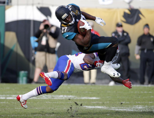 <p>Jacksonville Jaguars running back Leonard Fournette (27) makes a reception over Buffalo Bills defensive back Leonard Johnson in the second half of an NFL wild-card playoff football game, Sunday, Jan. 7, 2018, in Jacksonville, Fla. (AP Photo/Stephen B. Morton) </p>