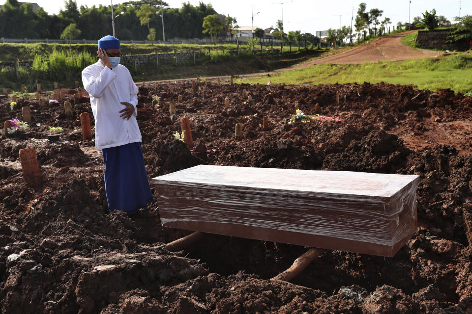 An Islamic cleric recites the call of prayer during the burial of a man at the special section of Jombang Public Cemetery reserved for those who died of COVID-19, in Tangerang on the outskirts of Jakarta, Indonesia,Monday, June 21, 2021. Indonesia saw significant spikes in confirmed COVID-19 cases recently, an increase blamed on travel during last month's Eid al-Fitr holiday as well as the arrival of new virus variants, such as the the Delta version first found in India. (AP Photo/Tatan Syuflana)