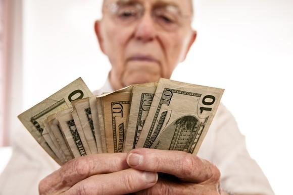 A senior man counting cash in his hands.
