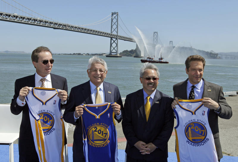 From left, Golden State Warriors owner and CEO Joe Lacob, NBA Commissioner David Stern, San Francisco Mayor Ed Lee and Warriors owner Peter Guber hold up 2017 jerseys following an announcement Tuesday, May 22, 2012, in San Francisco, that the NBA basketball team wants to build a new arena on the waterfront in San Francisco.  The Warriors unveiled plans to build an arena at Piers 30-32. The waterfront site is just blocks from the San Francisco Giants' ballpark and the downtown financial district. The arena is expected to be completed by 2017. (AP Photo/Eric Risberg)
