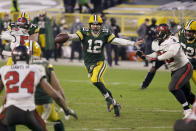 Green Bay Packers quarterback Aaron Rodgers (12) evades a tackle as he looks to pass against the Tampa Bay Buccaneers during the second half of the NFC championship NFL football game in Green Bay, Wis., Sunday, Jan. 24, 2021. (AP Photo/Mike Roemer)
