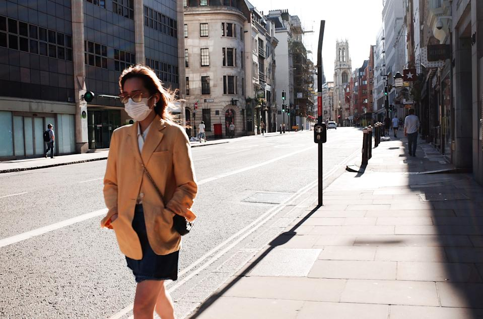 A woman wearing a face mask walks along a near-deserted Fleet Street in London, England, on May 29, 2020. The UK is now in its tenth week of coronavirus lockdown, with total deaths after a positive covid-19 test now standing at 38,161, according to today's updated count from the Department of Health and Social Care. In England, a raft of eased restrictions are due to go into effect from Monday, including permission for groups of up to six people to meet outdoors. English primary schools are also due to resume for some year groups from next week, in a move that has been met with significant pushback from teachers' unions and parents. (Photo by David Cliff/NurPhoto via Getty Images)
