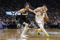 Denver Nuggets' Nikola Jokic (15) drives to the basket against Milwaukee Bucks' Robin Lopez during the first half of an NBA basketball game Friday, Jan. 31, 2020, in Milwaukee. (AP Photo/Aaron Gash)