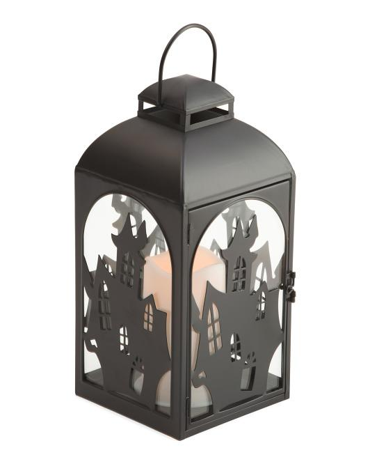 Black iron lantern with haunted house designs carved on all four sides with a faux fandle in the center