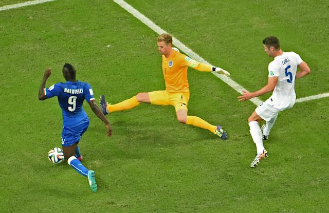 England's Gary Cahill, right, looks on as Italy's Mario Balotelli, left, and England's goalkeeper Joe Hart challenge for the ball during the group D World Cup soccer match between England and Italy at the Arena da Amazonia in Manaus, Brazil, Saturday, June 14, 2014. (AP Photo/Francois Xavier Marit, pool)