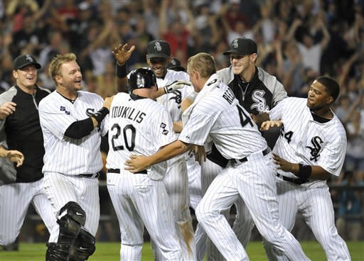 Chicago White Sox's Kevin Youkilis, center, is mobbed by teammates after hitting a game-winning RBI-single, scoring Alejandro De Aza, during the 10th inning of a baseball game against the Texas Rangers, Wednesday, July 4, 2012, in Chicago. (AP Photo/Brian Kersey)