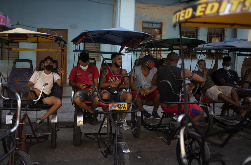 Bicycle taxi drivers sit on their bikes as they wait for customers in Old Havana, Cuba, Monday, July 12, 2021, the day after protests against food shortages and high prices amid the coronavirus crisis. (AP Photo/Eliana Aponte)