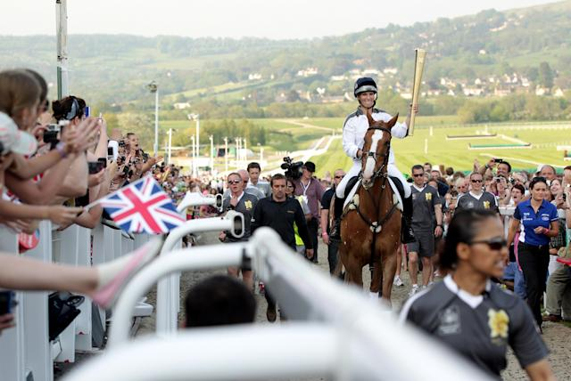 CHELTENHAM, UNITED KINGDOM - MAY 23: In this handout image provided by LOCOG, Olympic Torchbearer Zara Phillips carries the Olympic Flame whilst riding her horse Toytown on day 5 of the 70 day Olympic Torch Relay tour of the UK at Cheltenham Racecourse on May 23, 2012 in Cheltenham, England. The Olympic Flame arrived in the UK last Friday and will involve 8,000 torchbearers covering 8,000 miles. (Photo by LOCOG via Getty Images)