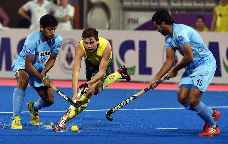 India's Uthappa Sannuvanda (L) and  Dharamvir Singh (R) block Australia's Flynn Ogilvie during their Champions Trophy match for 3rd and 4th place in Bhubaneswar in December 2014