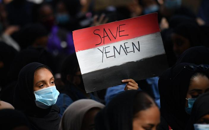 A protester holds a Yemeni flag-themed placard in Parliament Square in London - JUSTIN TALLIS/AFP via Getty Images