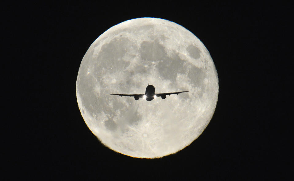 "A passenger aircraft, with the full ""Harvest Moon"" seen behind, makes its final approach to landing at Heathrow Airport in west London, September 19, 2013. The Harvest Moon is a traditional name for the full moon that is closest to the autumn equinox, and at a traditional period where farmers would be harvesting crops. The moon's rise time and angle of path give the illusion that the Harvest Moon is both closer, larger and brighter; though actually it is not. REUTERS/Toby Melville (BRITAIN - Tags: TRANSPORT SOCIETY TPX IMAGES OF THE DAY)"