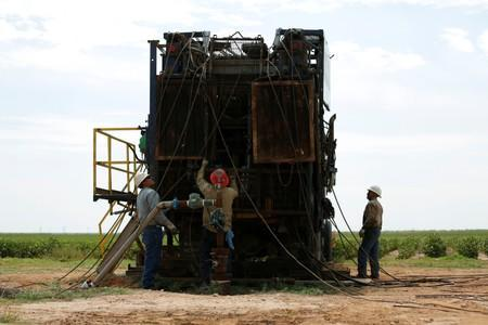 Oil field workers prepare a swabbing rig in a cotton field in Seminole