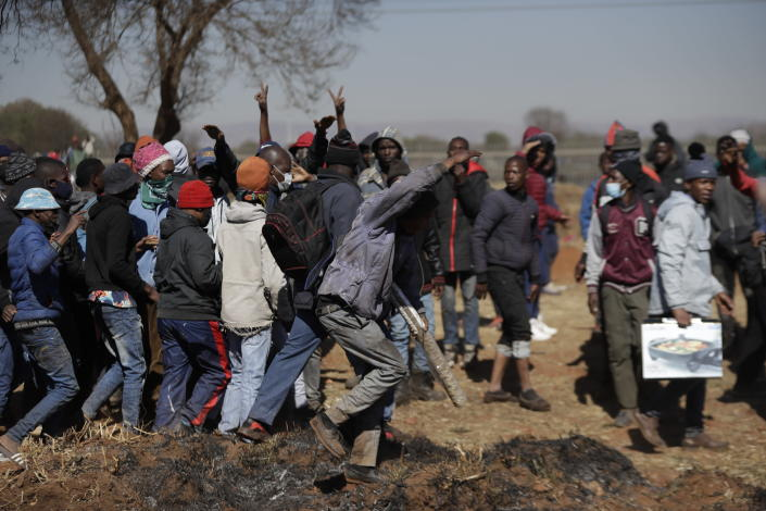 A group of men shout as they try to enter a shopping mall in Vosloorus, east of Johannesburg, South Africa, Wednesday July 14, 2021. South Africa's rioting continued Wednesday as police and the military struggle to quell the violence in Gauteng and KwaZulu-Natal provinces. The violence started in various parts of KwaZulu-Natal last week when Zuma began serving a 15-month sentence for contempt of court. (AP Photo/Themba Hadebe)