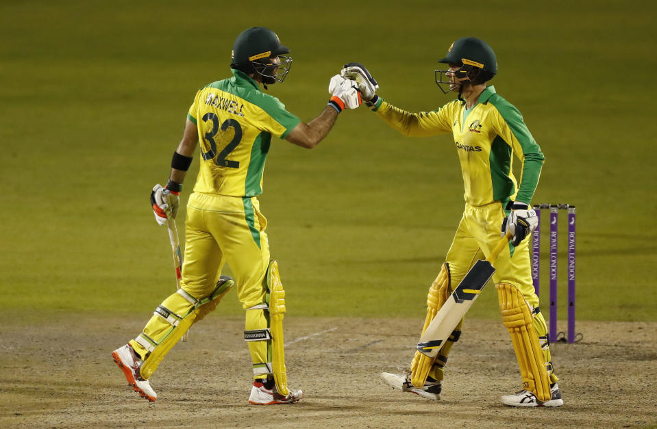 Australia's Glenn Maxwell, left, celebrates with batting partner Alex Carey after scoring a century during the third ODI cricket match between England and Australia, at Old Trafford in Manchester, England, Wednesday, Sept. 16, 2020. (Jason Cairnduff/Pool via AP)