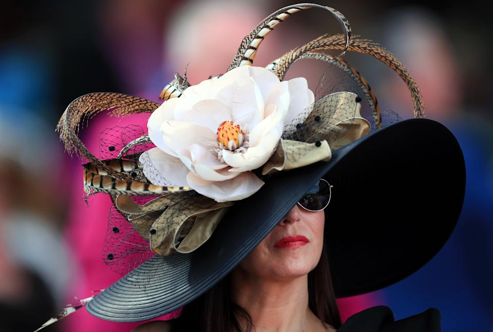 A woman's face is partially shielded by a large hat with many flowers and feathers.