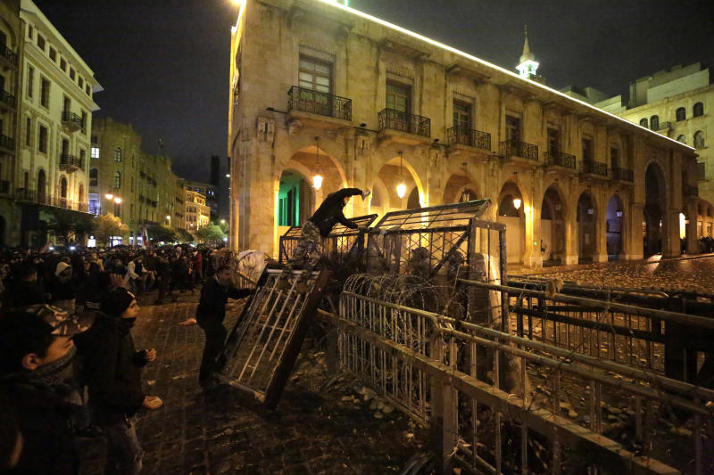 An anti-government protester stands on barriers as he throws stones against riot police during ongoing protests against the political elites who have ruled the country for decades, in Beirut, Lebanon, Sunday, Jan. 19, 2020. (AP Photo/Hassan Ammar)