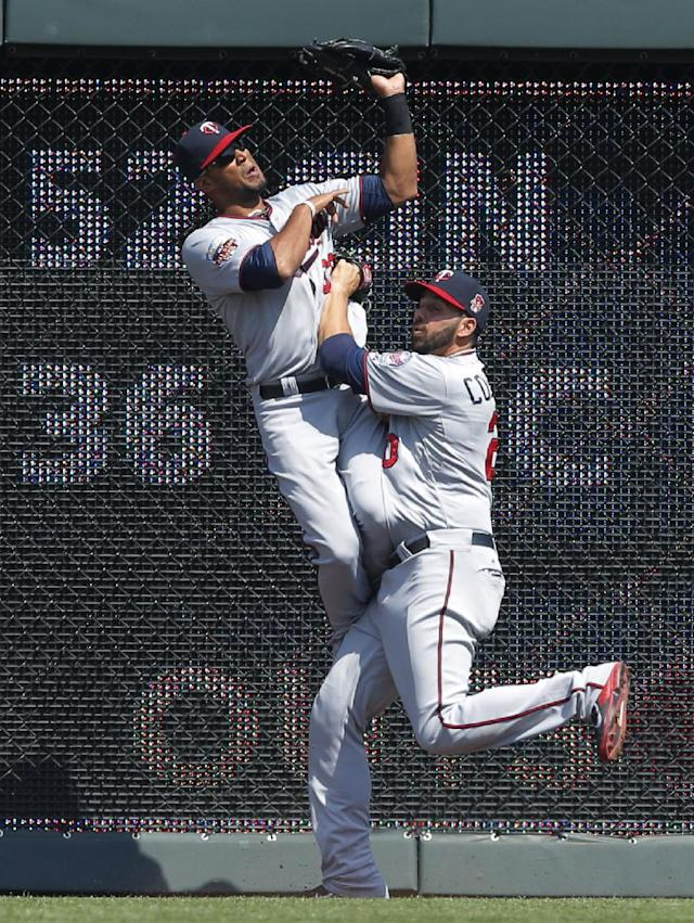 Minnesota Twins center fielder Aaron Hicks, left, catches a fly ball hit by Kansas City Royals' Mike Moustakas, over teammate Chris Colabello during the fifth inning of a baseball game at Kauffman Stadium in Kansas City, Mo., Saturday, April 19, 2014. (AP Photo/Orlin Wagner)