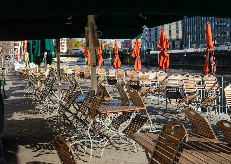 Closed parasols, empty tables and folded away chairs at a restaurant on the banks of the Spree, a tributary of River Havel, in Berlin. Photo: Jens Kalaene/Picture Alliance via Getty