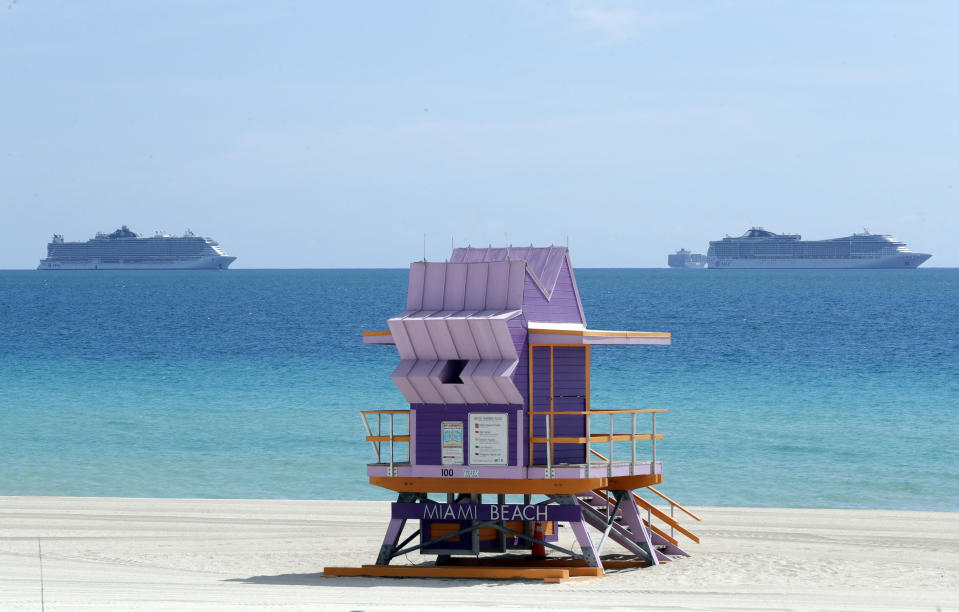 Two cruise ships are anchored offshore past a lifeguard tower, Tuesday, March 31, 2020, in Miami Beach, Fla. (AP Photo/Wilfredo Lee)